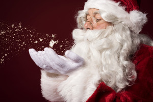 Santa claus blowing some snowflakes