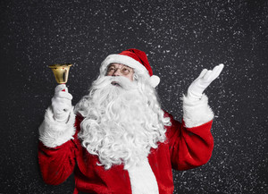 Santa claus with handbell among snow falling