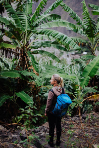 Santo antao island. Cape verde. Blond young women with blue backpack walking through banana plantation on the trekking trail route to Paul valley