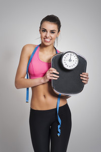 Satisfied fit woman with weight scale