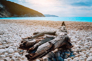 Scenic view of Myrtos beach at sunny summer day. Beautiful mediterranean landscape on Kefalonia island, Greece. Snag on the foreground