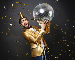 Screaming man with birthday hat holding disco ball