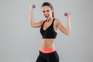 Screaming sports woman with dumbbells over gray background
