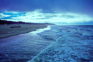 Sea shore in stormy weather. Beautiful dramatic sky over beach, blue toned