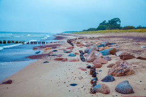 Sea shore, sand with pebbles. Deserted beach. Marine landscape with blue ocean and beautiful cloudy sky.