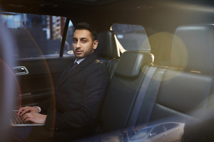 Self-employed businessman networking in taxi cab