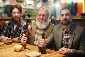 Senior and young men with beards toasting for Patrick day