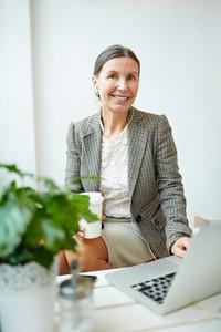 Senior businesswoman having coffee break in cafe