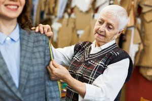 Senior fashionist measuring length of her client jacket sleeve