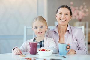 Senior female and her granddaughter having dessert or snack by table