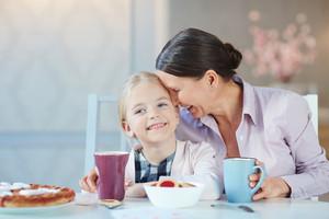 Senior female and her happy granddaughter having dessert and drinks