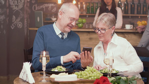 Senior man showing something on his phone to his wife in a restaurant. Cheerful senior couple. Romantic couple.