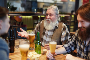 Senior man talking to guys in pub by glass of beer