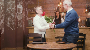 Senior man with flowers for his wife. Romantic couple. Senior couple in their sixties.