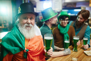 Senior man with grey beard cheering up with glass of beer