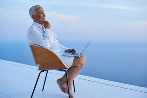 senior man working on laptop computer and looking ocean view sunset on balcony of modern home