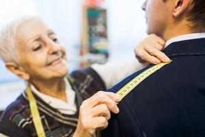 Senior tailor measuring shoulder width of male jacket
