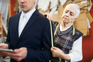 Senior tailor taking measures from jacket sleeve