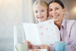 Senior woman and little girl with greeting card looking at camera