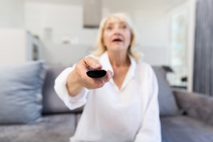 Senior woman changing channel with remote control while sitting on a sofa at home