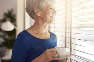 Senior woman drinking coffee next to the window