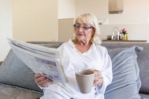Senior woman in eyeglasses reading a newspaper while having a cup of coffee in the morning on a couch a home