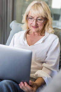 Senior woman in eyeglasses using laptop computer while sitting on a couch at home