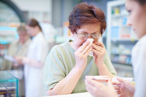 Senior woman sneezing in tissue in pharmacy