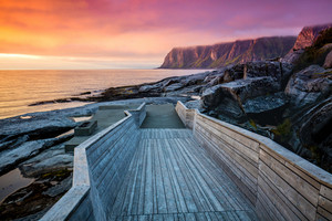 Senja island at orange sunset. Wooden pathway on the rocky beach