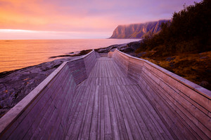 Senja island at sunset light. Wooden pathway on the rocky beach.