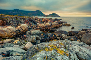 Senja island at sunset. Wild rocky beach