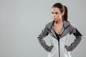 Serious female runner in warm clothes holding hands on hip and looking away over gray background