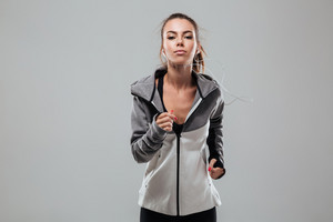 Serious female runner in warm clothes running in studio and looking at the camera over gray background