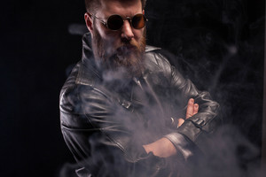 Serious portrait of handsome bearded man wearing a black leather jacket over black background. Attractive young man.
