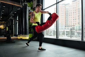 Serious young sportsman doing exercises with punching bag at the gym