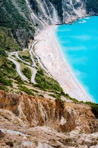 Serpentine zigzag road down to famous Myrtos Beach. Many tourists on the sunny beach, Kefalonia, Greece