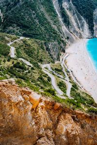 Serpentine zigzag road down to famous Myrtos Beach. Orange rocks ravine on side. Sunny beach from view point platform, Kefalonia, Greece