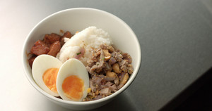 Serving Asian style soup with rice, pork, hardboiled egg and eggplant by pouring hot stock