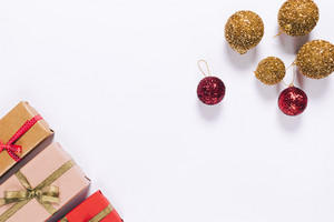 Several gift boxes in wrapping paper with ribbon and Christmas balls on white background, top view