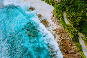 Seychelles Mahe island aerial drone landscape of coastline paradise sandy beach with palm trees and beautiful clear blue ocean waves rolling against granite rocks. Shallow dreamlike lagoon