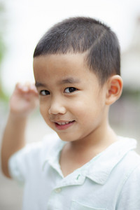 shallow depth of field photography of lovely asian boy toothy smiling face with relaxing emotion