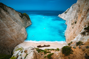 Shipwreck in Navagio beach. Azure turquoise sea water and paradise sandy beach. Famous tourist visiting landmark on Zakynthos island, Greece