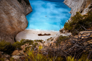 Shipwreck in Navagio beach. Azure turquoise sea water surrounded by huge rocks. Famous tourist visiting landmark on Zakynthos island, Greece