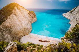Shipwreck on Navagio beach. Azure turquoise sea water and paradise like sandy beach. Famous tourist landmark on Zakynthos island, Greece