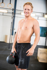 Shirtless Male Athlete Lifting Kettlebell In Health Club