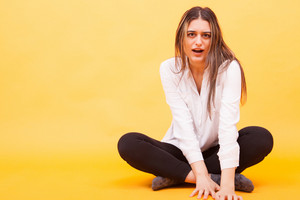 Shocked amazed young woman in white shirt sitting down over yellow background. Beautiful girl