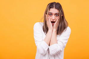 Shocked amazed young woman with hands on head over yellow background