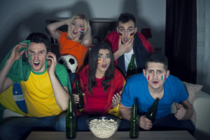 Shocked friends from different country watching soccer match on TV