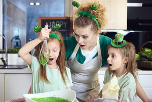 Shocked mother with daughters mixing fondant icing
