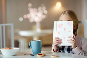 Shy girl hiding her face behind paper card with drawn red hearts